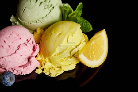 Photo for Delicious lemon, berry and mint ice cream balls isolated on black - Royalty Free Image