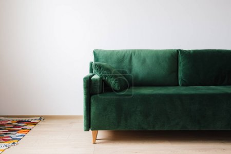 Photo for Green sofa with pillow near colorful rug on floor - Royalty Free Image