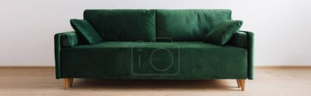 modern green sofa with pillows in room, panoramic shot