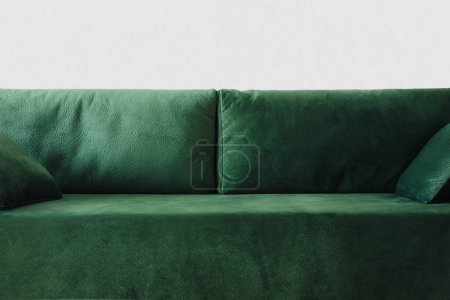 Foto de Cerca de un moderno sofá verde con almohadas en la habitación. - Imagen libre de derechos