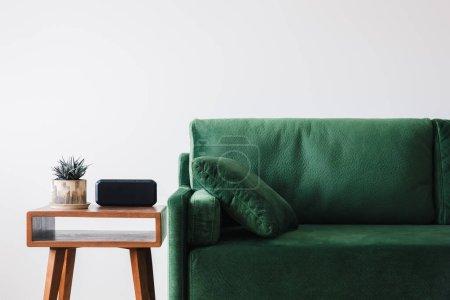 Photo pour Vue rapprochée du canapé vert avec oreiller et table basse en bois avec plante et réveil - image libre de droit