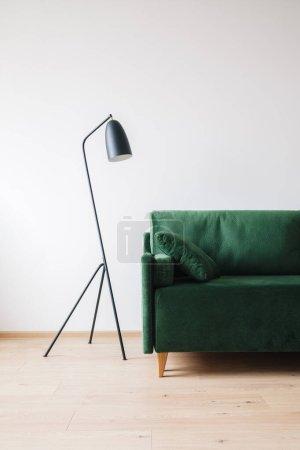 Photo pour Canapé vert avec oreiller près du lampadaire moderne en métal - image libre de droit