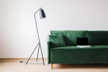 Photo for Green sofa with pillow and laptop with blank screen on books near metal modern floor lamp - Royalty Free Image