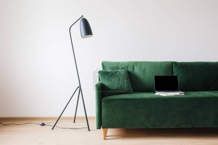 Foto de Sofá verde con almohada y portátil con pantalla en blanco en libros cerca de la lámpara de pie moderna de metal - Imagen libre de derechos