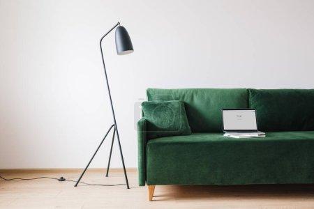 KIEW, UKRAINE - 14. APRIL 2020: grünes Sofa mit Kissen und Laptop mit Google-Website auf dem Bildschirm in der Nähe von Metall moderne Stehlampe