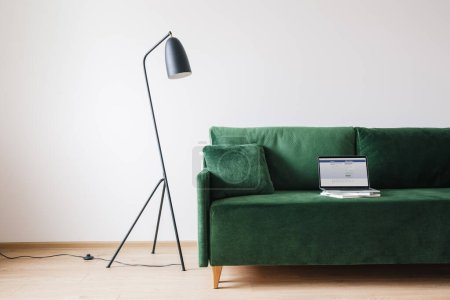 Photo for KYIV, UKRAINE - APRIL 14, 2020: green sofa with pillow and laptop with Facebook website on screen near metal modern floor lamp - Royalty Free Image