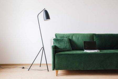KIEW, UKRAINE - 14. APRIL 2020: grünes Sofa mit Kissen und Laptop mit Javascript auf dem Bildschirm in der Nähe von Metall moderne Stehlampe