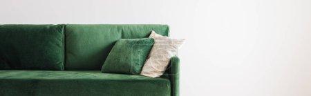 Photo pour Canapé vert moderne avec oreillers dans une chambre spacieuse près de la paroi grise, vue panoramique - image libre de droit