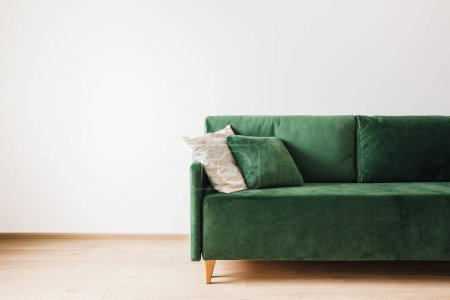 modern green sofa with pillows in spacious room