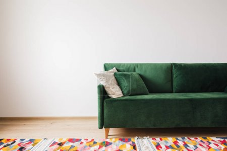 Photo for Modern green sofa with pillows in spacious room with colorful rug - Royalty Free Image