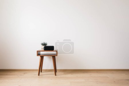 Photo for Wooden coffee table with plant and clock with blank screen - Royalty Free Image