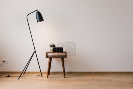 Photo for Metal floor lamp and wooden coffee table with plant and clock with blank screen - Royalty Free Image
