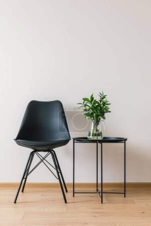 Photo for Black coffee table with green plant near modern chair - Royalty Free Image