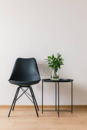 Photo pour Table à café noire avec plante verte près d'une chaise moderne - image libre de droit