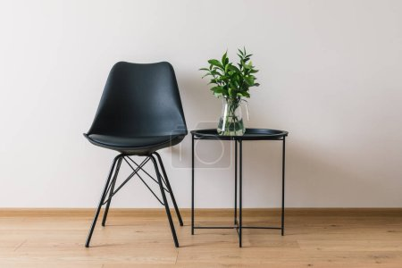 black coffee table with green plant near modern chair