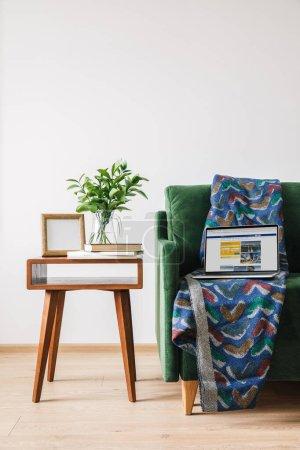 Photo pour KYIV, UKRAINE - 14 AVRIL 2020 : canapé vert avec couverture et ordinateur portable avec site de réservation près de la table basse en bois avec plante verte, livres et cadre photo - image libre de droit