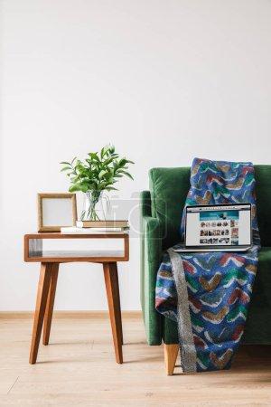 Photo pour KIEV, UKRAINE - 14 AVRIL 2020 : canapé vert avec couverture et ordinateur portable avec site web amazon près d'une table basse en bois avec plante verte, livres et cadre photo - image libre de droit