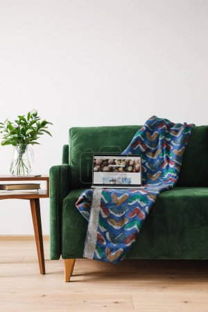 Photo for KYIV, UKRAINE - APRIL 14, 2020: green sofa with blanket and laptop with depositphotos website near wooden coffee table with green plant - Royalty Free Image
