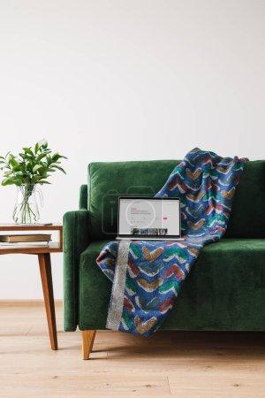 Photo pour KYIV, UKRAINE - 14 AVRIL 2020 : canapé vert avec couverture et ordinateur portable avec site web airbnb près de la table basse en bois avec plante verte - image libre de droit
