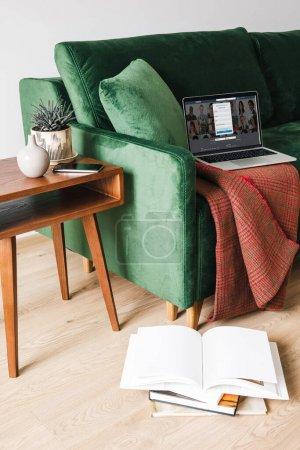 Photo pour KYIV, UKRAINE - 14 AVRIL 2020 : canapé vert avec couverture et ordinateur portable avec LinkedIn près de la table basse en bois avec plante et smartphone près des livres sur le sol - image libre de droit