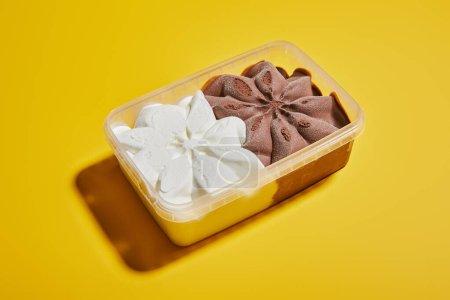 Photo pour Crème glacée brune et blanche fraîche dans un récipient sur fond jaune - image libre de droit