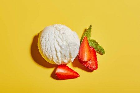 Photo pour Vue de dessus de la boule de crème glacée savoureuse fraîche avec des feuilles de menthe et de fraise sur fond jaune - image libre de droit