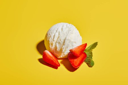 Photo for Fresh tasty ice cream ball with mint leaves and strawberry on yellow background - Royalty Free Image