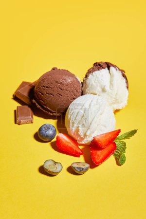 Photo pour Délicieuse crème glacée brune et blanche aux baies, chocolat et menthe sur fond jaune - image libre de droit