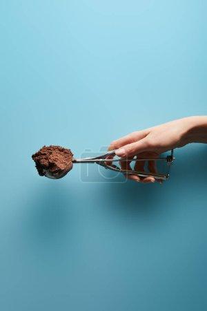 Photo pour Vue recadrée de femme tenant cuillère avec crème glacée au chocolat sur fond bleu - image libre de droit
