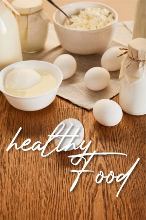 Photo for Selective focus of various fresh organic dairy products and eggs on rustic wooden table with healthy food illustration - Royalty Free Image