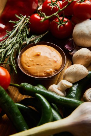 Photo for Delicious sauce in bowl near fresh ripe vegetables, rosemary and mushrooms - Royalty Free Image