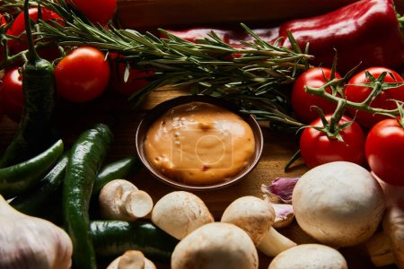 delicious sauce in bowl near fresh ripe vegetables, rosemary and mushrooms