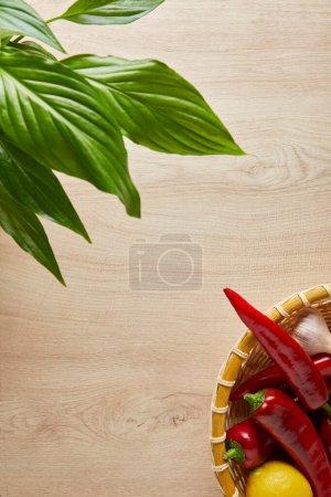 Photo pour Vue de dessus des feuilles vertes et des légumes frais mûrs dans le panier sur la table en bois - image libre de droit
