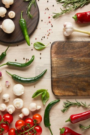 Photo for Top view of empty board near fresh ripe vegetables, herbs, spices and mushrooms on wooden table - Royalty Free Image