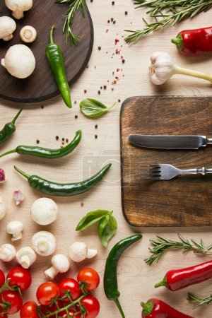 Photo for Top view of cutlery on board near fresh ripe vegetables, herbs, spices and mushrooms on wooden table - Royalty Free Image