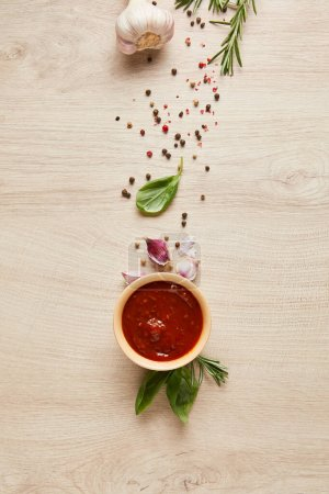 Photo for Top view of delicious tomato sauce in bowl near herbs and spices on wooden table - Royalty Free Image