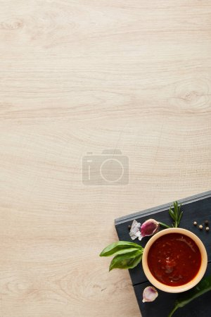 top view of delicious tomato sauce in bowl near herbs and spices on board on wooden table