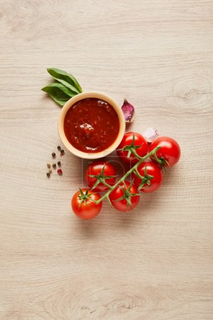 top view of delicious tomato sauce in bowl near spices and tomatoes on wooden table