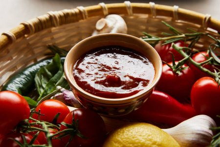 Photo for Delicious tomato sauce with fresh ripe vegetables in basket - Royalty Free Image