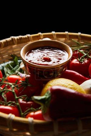 selektiver Schwerpunkt köstlicher Tomatensauce mit frischem reifem Gemüse im Korb isoliert auf schwarz