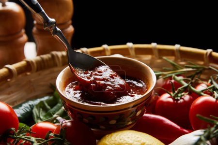 close up view of delicious tomato sauce with spoon near fresh ripe vegetables in basket isolated on black