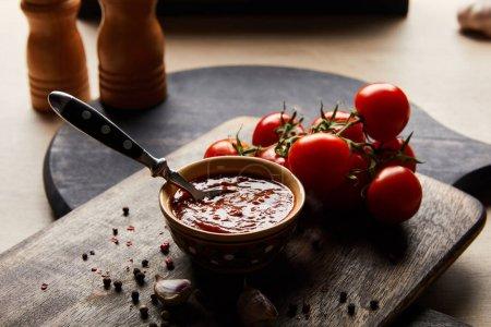 selektiver Schwerpunkt köstlicher Tomatensauce in Schüssel mit Löffel in der Nähe von Tomaten und Gewürzen auf Holzbrett