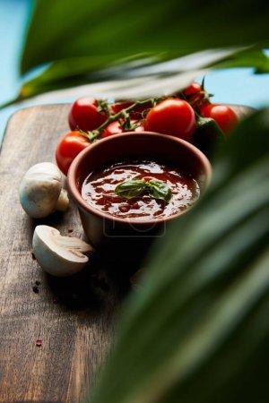 selektiver Fokus auf grüne Blätter und köstliche Tomatensauce in Schüssel auf Holzbrett mit frischem reifem Gemüse auf blauem Hintergrund
