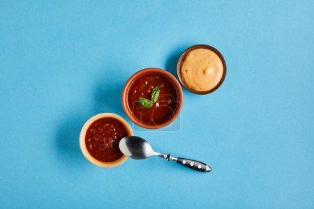 Draufsicht auf köstliche Saucen in Schüsseln mit Löffel auf blauem Hintergrund