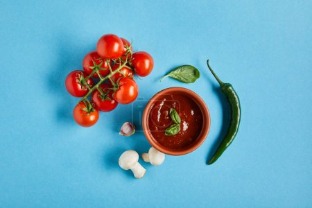 top view of delicious tomato sauce in bowl near fresh ripe vegetables on blue background