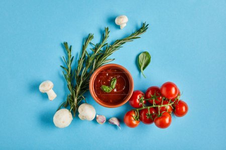 Photo for Top view of delicious tomato sauce in bowl near fresh ripe vegetables on blue background - Royalty Free Image