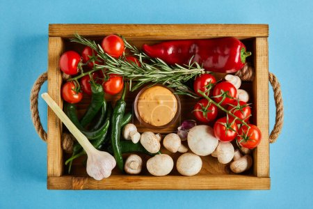 Photo for Top view of delicious sauce in bowl near fresh ripe vegetables, rosemary and mushrooms in wooden box on blue background - Royalty Free Image