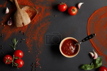 Photo for Top view of tomato paste in bowl near cherry tomatoes, garlic cloves, paprika powder, rosemary and basil leaves on black - Royalty Free Image