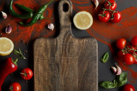 Photo for Top view of cherry tomatoes, garlic cloves, lemons, green chili peppers, paprika powder and basil leaves near wooden cutting board on black - Royalty Free Image