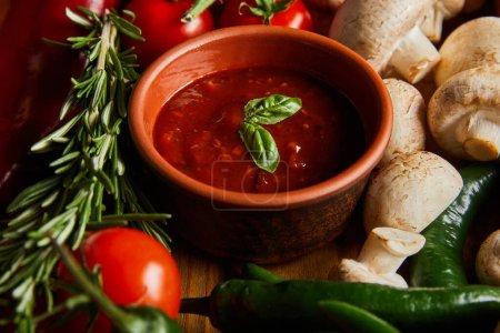 Photo pour Accent sélectif de la sauce tomate avec des feuilles de basilic près de tomates cerises, piment vert, champignons et romarin - image libre de droit